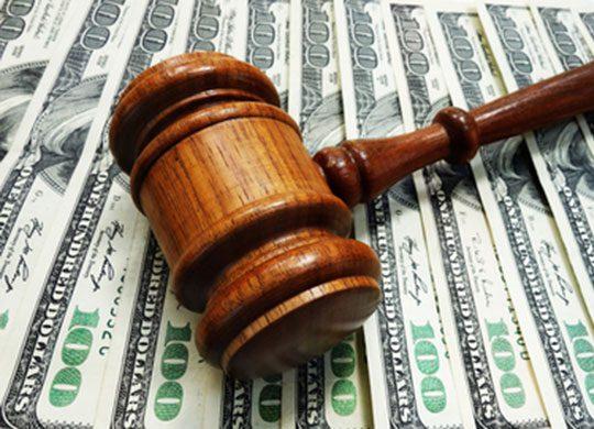 Photo of court gavel alongside $100 dollar bills